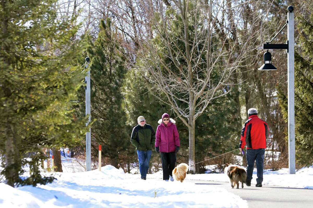 Paul and Kathy McElligott of Latham, left, cross paths with Terry Brown of Latham and his two Shetland sheepdogs, Ziggy and Jenna, during a sunny walk on Thursday, March 6, 2014, at The Crossings in Colonie, N.Y. (Cindy Schultz / Times Union)