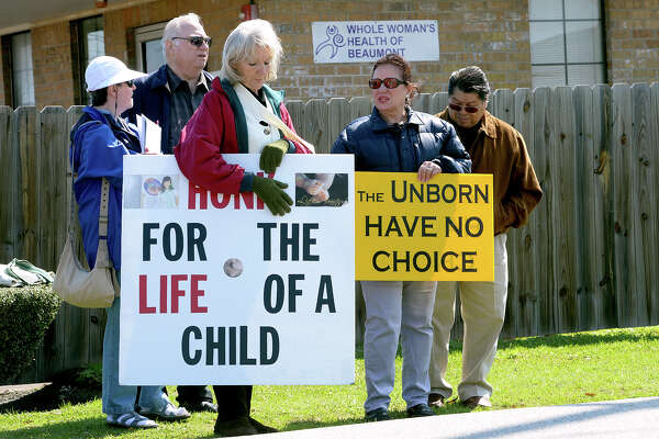 Eileen Romano, foreground, holds an antiabortion sign in front of the Whole Woman's Health of Beaumont clinic on Thursday. On Wednesday, clinic operators announced the facility's closure due to strict state laws. From left, Judy Alciatore, Paul Alciatore, Yvette Estrada and Rolando Estrada hold signs. Photo taken Thursday, March 06, 2014 Guiseppe Barranco/@spotnewsshooter