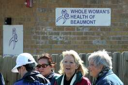 From left, Judy Alciatore, Yvette Estrada, Eileen Romano, and Sherry Maniscalco holds signs in front of the Whole Woman's Health of Beaumont clinic on Thursday. On Wednesday, clinic operators announced the facility's closure due to strict state laws.  Photo taken Thursday, March 06, 2014 Guiseppe Barranco/@spotnewsshooter