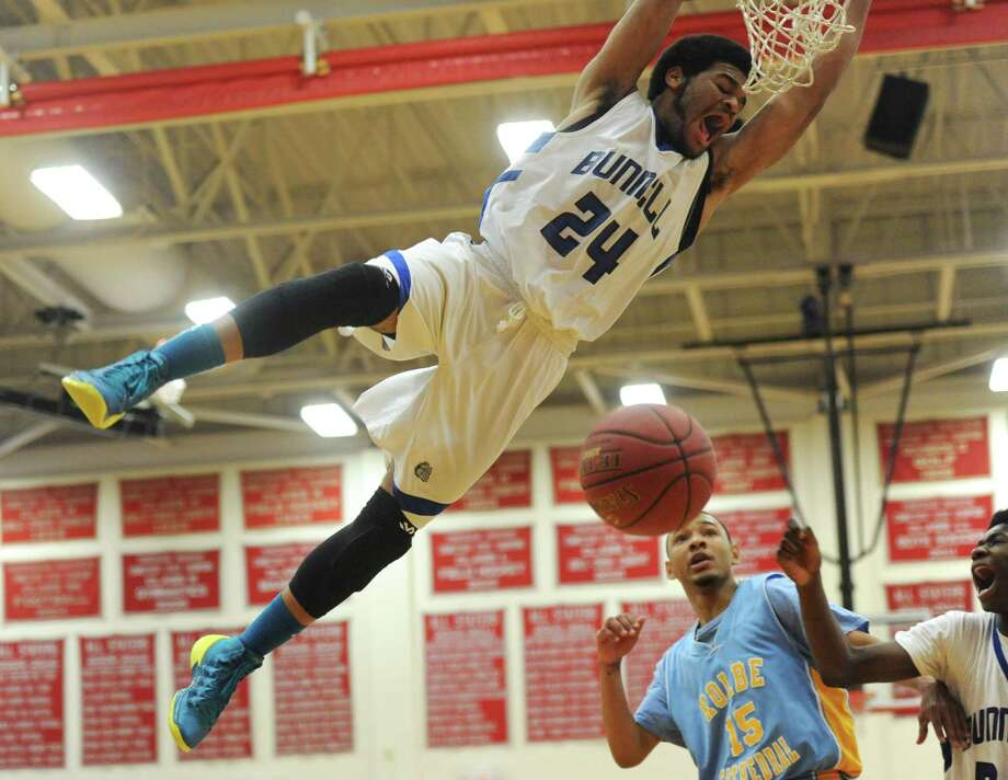 Bunnell's Donte Peeler hangs from the rim during a dunk in the SWC boys basketball championship game between No. 2 Bunnell and No. 5 Kolbe Cathedral at Pomperaug High School in Southbury, Conn. Thursday, March 6, 2014. Photo: Tyler Sizemore / The News-Times