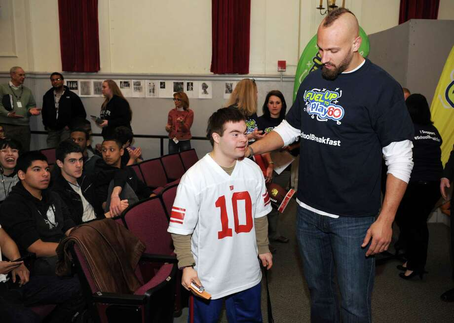 Stamford ( Conn. ) High School student Joe Lupinacci  talks to Mark Herzlich, linebacker for the New York Giants, at a assembly where Herzlich spoke with students about how school breakfast can help them reach their full potential on Friday March 7, 2014. Photo: Dru Nadler / Stamford Advocate Freelance