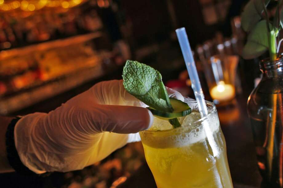 Bartender Bryan Shoffit demonstrates how he would have to garnish a drink with cucumber and mint while using a latex glove while behind the bar at 15 Romolo in San Francisco, Calif., on Wednesday, March 5, 2014. A new glove law was passed in January that requires any restaurant worker or bartender who prepares ready-to-eat food or drinks to wear gloves. The law has received so much blow back that the people who passed the legislation are now trying to repeal it. But until that happens, starting in June, the food industry has to adhere to the new rules. Photo: Carlos Avila Gonzalez, The Chronicle