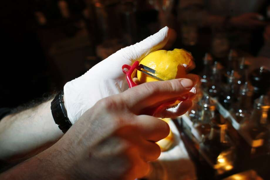 Bartender Bryan Shoffit peels the rind from a lemon as he demonstrates a using a latex glove on one hand while behind the bar at 15 Romolo in San Francisco, Calif., on Wednesday, March 5, 2014. A new glove law was passed in January that requires any restaurant worker or bartender who prepares ready-to-eat food or drinks to wear gloves. The law has received so much blow back that the people who passed the legislation are now trying to repeal it. But until that happens, starting in June, the food industry has to adhere to the new rules. Photo: Carlos Avila Gonzalez, The Chronicle