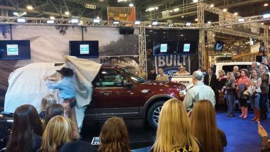 King Ranch cowboys Ricky Falcon and Robert Silguero remove the cover of Ford's redesigned 2015 Expedition King Ranch at RodeoHouston. Photo: Courtesy, Nik Ciccone