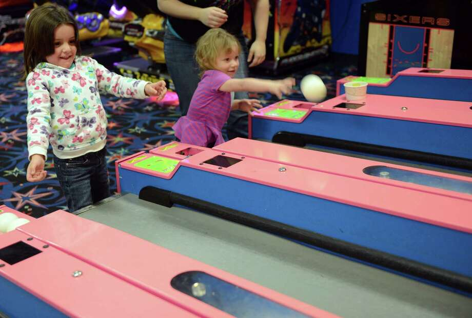 Four-year-old Kylie Tardy, of Oxford, and her sister Kasey, 2, play skee-ball Friday, Mar. 7, 2014, at the arcade at Sports Center of Connecticut in Shelton, Conn. Photo: Autumn Driscoll / Connecticut Post
