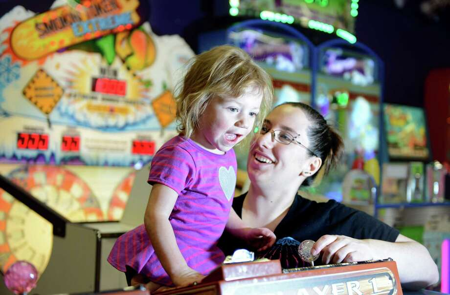 Jessica Skerrett, of Ansonia, holds her two-year-old niece Kasey Tardy, of Oxford, as they play a game Friday, Mar. 7, 2014, at the arcade at Sports Center of Connecticut in Shelton, Conn. Photo: Autumn Driscoll / Connecticut Post