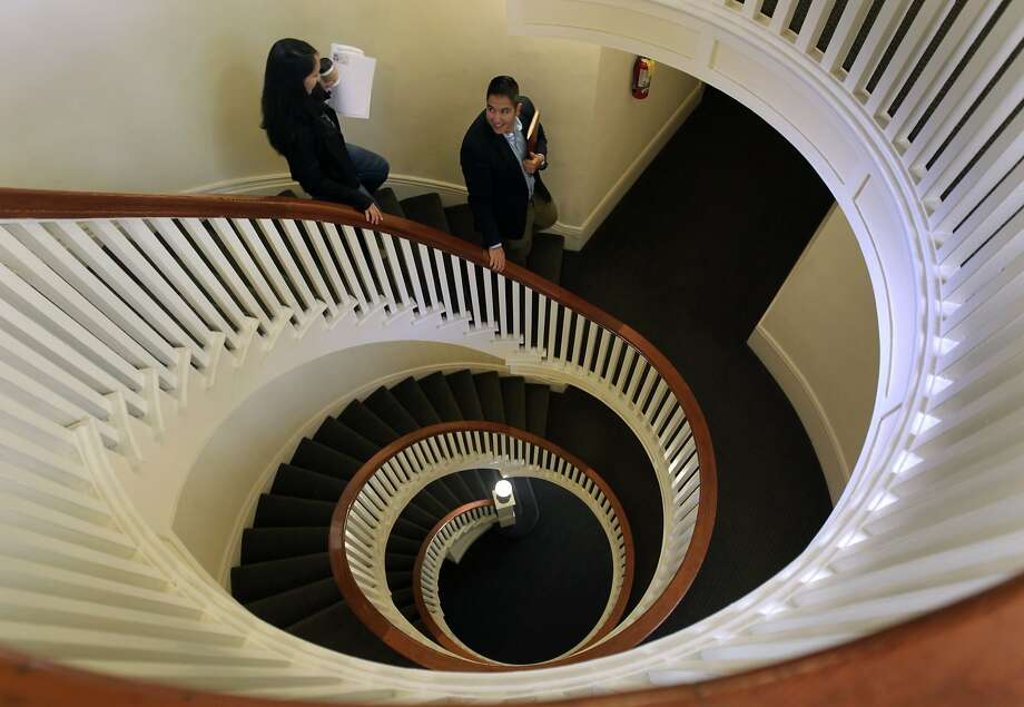 Sarah Gilbert walks down the central spiral staircase of a Mission District apartment building with property management representative Rafael Davis. Photo: Paul Chinn, The Chronicle
