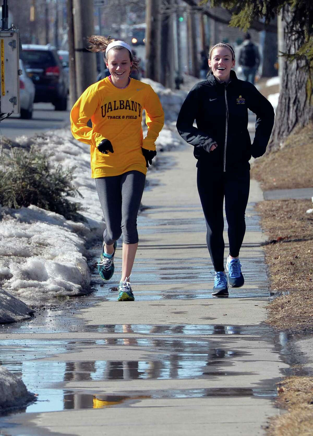 University at Albany track team members Hanna Smith, left, and Molly Pezzulo, right, are out for a practice run and some rare rays of sun as the run down Western Avenue Friday afternoon March 7, 2014 in Albany, N.Y. (Skip Dickstein / Times Union)