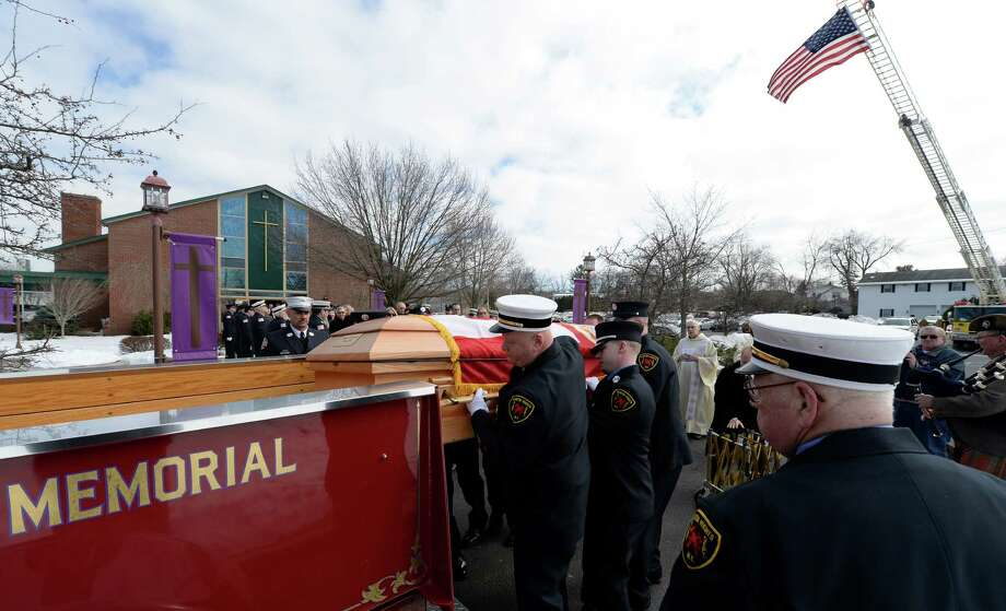 The casket carrying the remains of Stephen Gregory,  97, life member of the Clinton Heights Fire Department and retiree of the New York City Fire Department, is placed on a ceremonial pumper after his funeral service Friday morning, March 7, 2014, at St. Mary's Church in East Greenbush, N.Y.   (Skip Dickstein / Times Union) Photo: SKIP DICKSTEIN / 00026023A