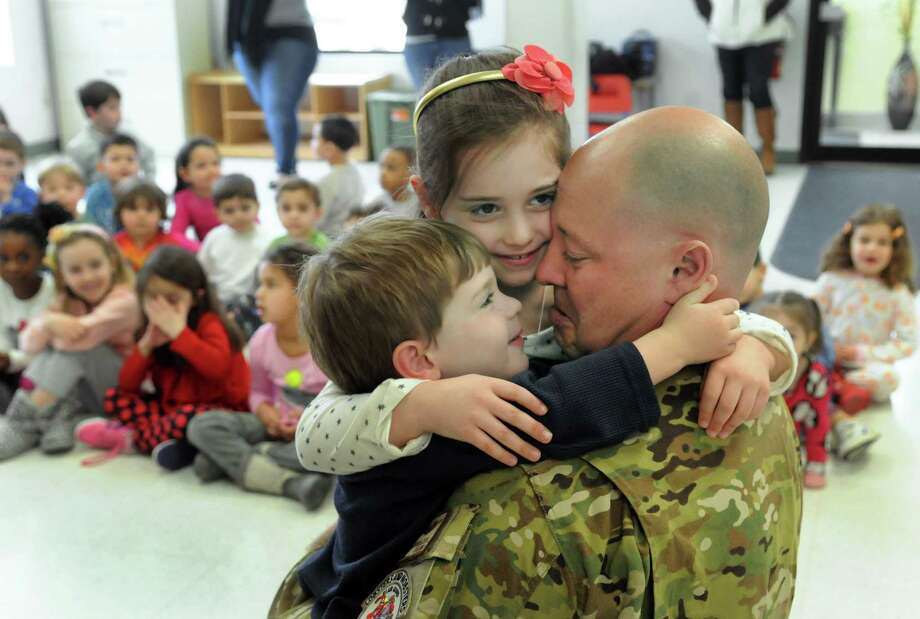 Christian, 3, and Jordyn Geanuracos, 6, hug their father after he surprised them with a visit to their school, New England Country Day School in Danbury, Conn. Friday, March 7, 2014. Thomas Geanuracos, 41, a Danbury police officer and Air National Guardsman stationed in Iraq for the past six months. Photo: Carol Kaliff / The News-Times
