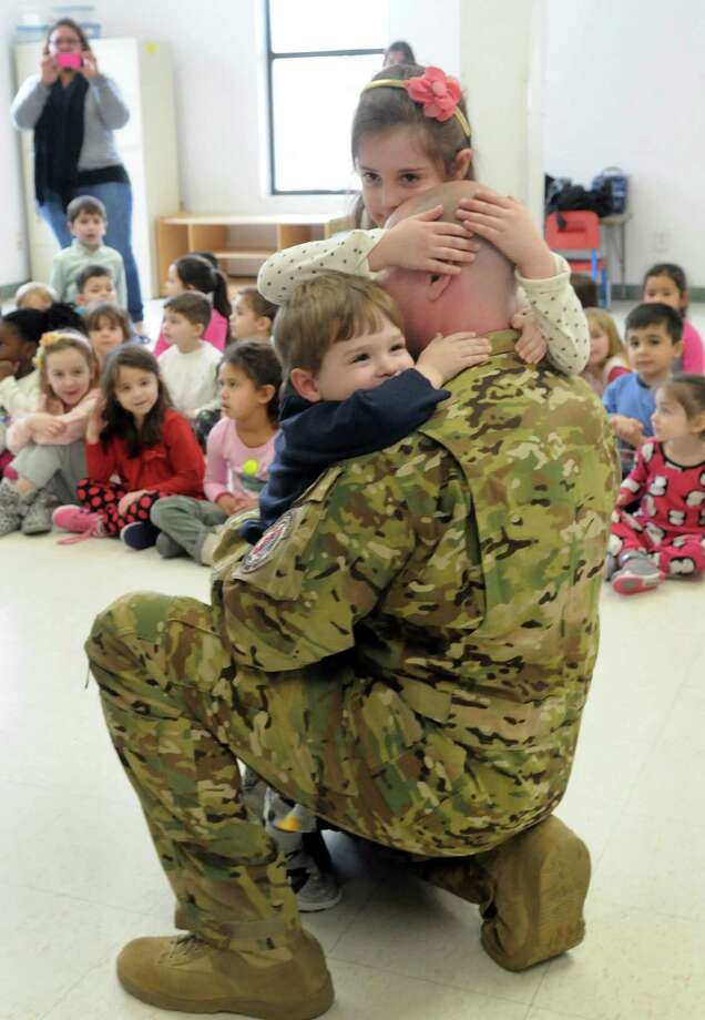 Thomas Geanuracos, 41, a Danbury police officer and Air National Guardsman stationed in Iraq, surprised his children, Jordyn, 6, and Christian, 3, at school, The New England Country Day School, Friday morning, March 7, 2014. He had been away almost six months. Photo: Carol Kaliff / The News-Times
