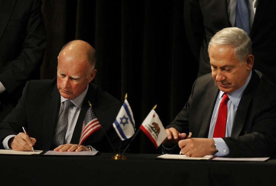 Gov. Jerry Brown (left) and Israeli Prime Minister Benjamin Netanyahu sign a pact while outside demonstrators protest Israel's policies on the Palestinians. Photo: Leah Millis, The Chronicle