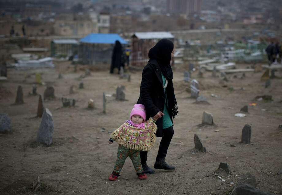 Not the best place to be a man or child either: An Afghan mother and child walk through 