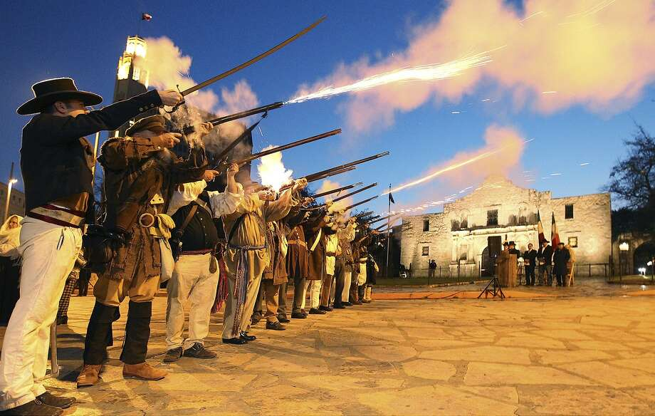 Remember the Alamo! San Antonio history buffs mark the 178th anniversary of the battle for Texas independence with a volley of musket fire in front of the famed citadel. Photo: Kin Man Hui, Associated Press