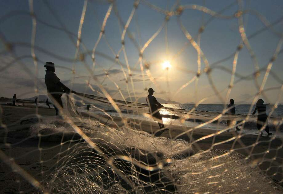 Fishermen pull their net from the sea as the sun sets on Gampong Jawa beach in Banda 