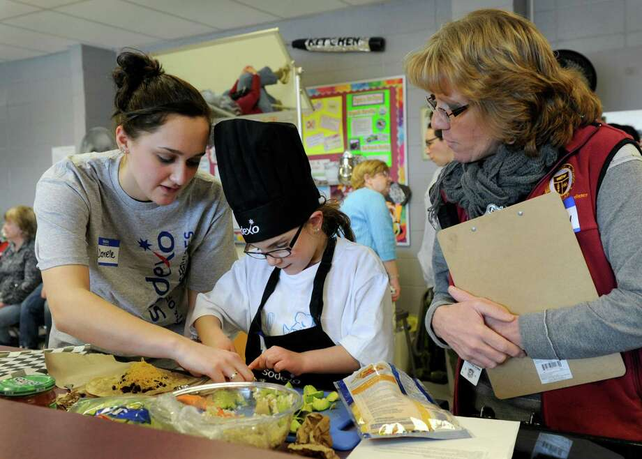 """Danielle Spinella, 17, left, a Bethel High senior, and Hannah Stowell, 8, a second-grader at Johnson School,  make Hannah's """"cheesy beansy wrap"""" during the Future Chefs competition held at the high school Friday. Betty Avery, right, health co-ordinator for the school district, is one of the judges. Hannah's sandwich took second place. Photo: Carol Kaliff / The News-Times"""
