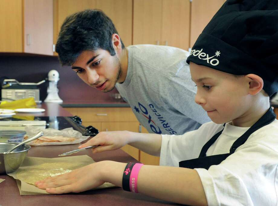 "Luke Cassavechia, 7, a first-grader at Rockewell School, makes his ""The Awesome Sandwich"" under the watchful eye of Joe Marji, 18, a Bethel High School senior. The two were competing in the Future Chefs competition at Bethel High School in Bethel Conn., Friday, March 7, 2014. Photo: Carol Kaliff / The News-Times"
