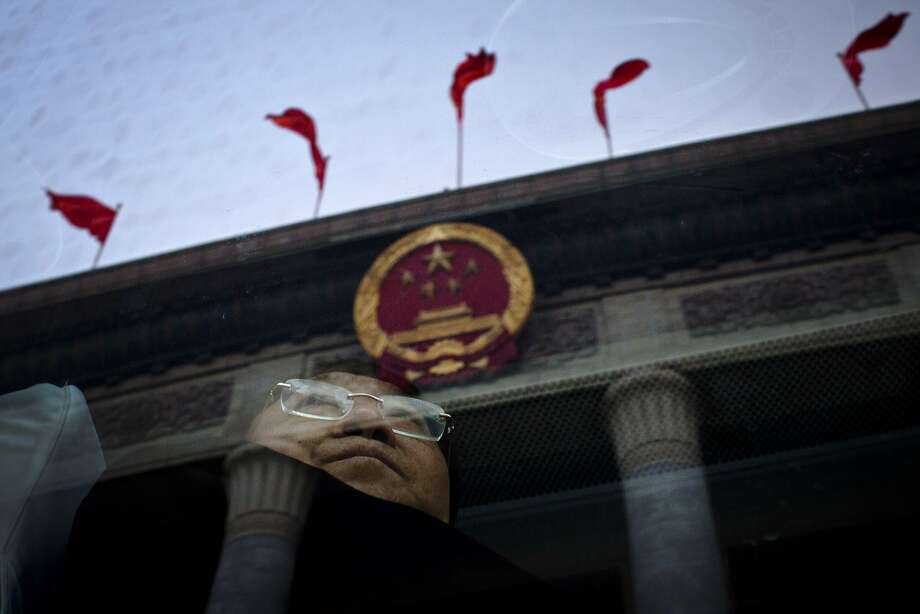 A delegate from southwestern China's Chongqing city waits on a bus to leave the Great Hall of the People, with Chinese national emblem and red flags on top of the venue reflected in the bus window, after a group discussion among city delegates as part of the National People's Congress in Beijing, Thursday, March 6, 2014. Photo: Alexander F. Yuan, Associated Press