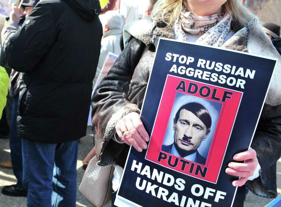 Pro-Ukrainian demonstrators marching in front of the White House on Thursday carry placards likening Russian President Vladimir Putin to Adolf Hitler. One of our readers says U.S. response to Russian aggression should be swift and substantial. Photo: Karen Bleier / Getty Images / AFP