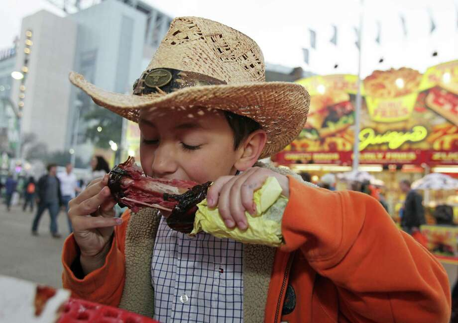 Eight-year-old Jason Llambes of Kingwood eats a turkey leg at the Houston Livestock Show and Rodeo carnival. Photo: James Nielsen, Staff / © 2014  Houston Chronicle