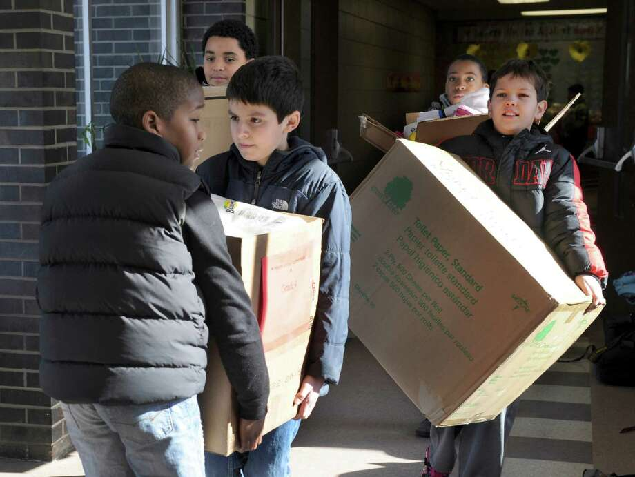 "From left, Xavier Ross, Johanse Martinez, Luis Amaya-Baylon, Cole Brown and Ryan Wunsch, carry boxes of collected items to be loaded into a car and donated to the Dorothy Day Hospitality House on Spring Street in Danbury, Conn. For the third year in a row, Shelter Rock School in Danbury has organized ""Hearts United Against Hunger,"" a way to mark the 100th day of school by giving back to the community. Photo: Carol Kaliff / The News-Times"