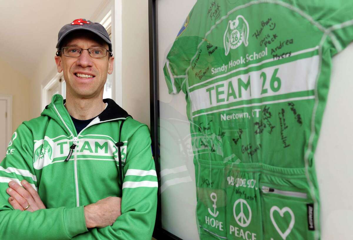 Monte Frank, a Sandy Hook bicyclist and assistant town attorney, is photographed at his Sandy Hook home, Thursday, March 6, 2014, standing next to a framed shirt from last year's Team 26 ride - signed by his teammates.