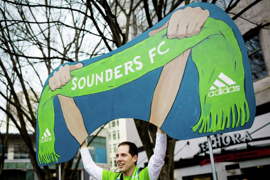 "Sounders FC fans gather and compete for scarves and jerseys at a ""Rave Rally"" Friday, March 7, 2014, at Westlake Park in Seattle. The Sounders home opener against Sporting KC kicks off Saturday at CenturyLink Field. Photo: JORDAN STEAD, SEATTLEPI.COM / SEATTLEPI.COM"