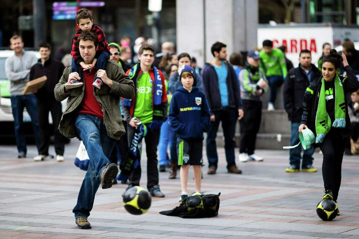 Sounders FC fans take shots on a goal during a
