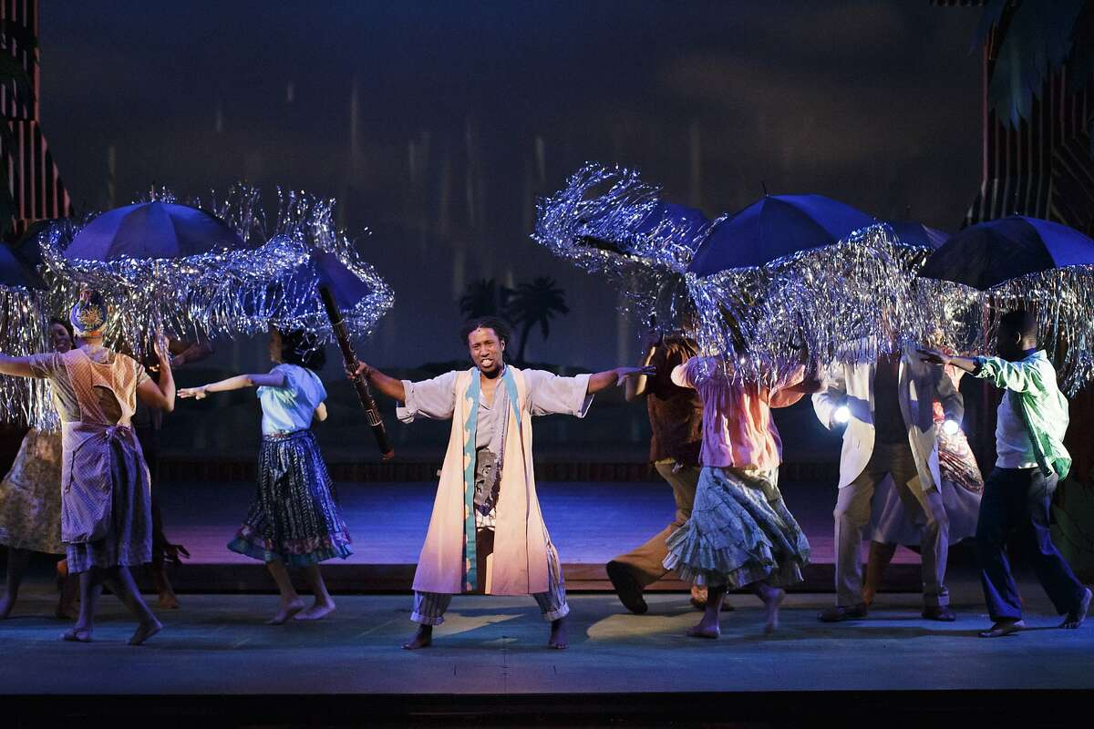 Omari Tau as Agwe, God of Water calls down a rain storm in the TheatreWorks production of the musical