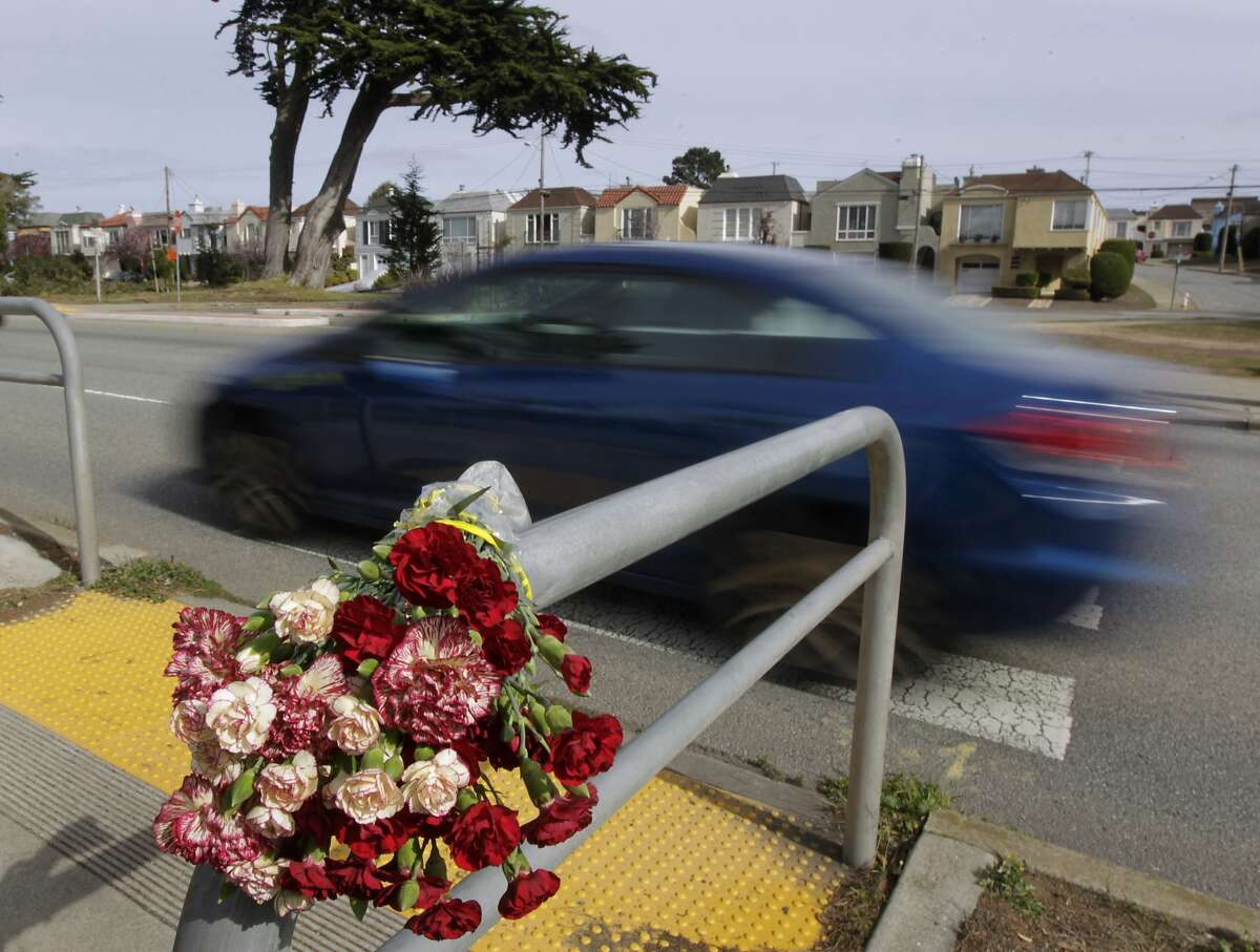A bouquet of flowers are left at the crosswalk at Sunset Boulevard and Yorba Street in San Francisco, Calif. on Wednesday, Feb. 5, 2014 one day after a pedestrian was hit and killed by a car traveling southbound on Sunset.
