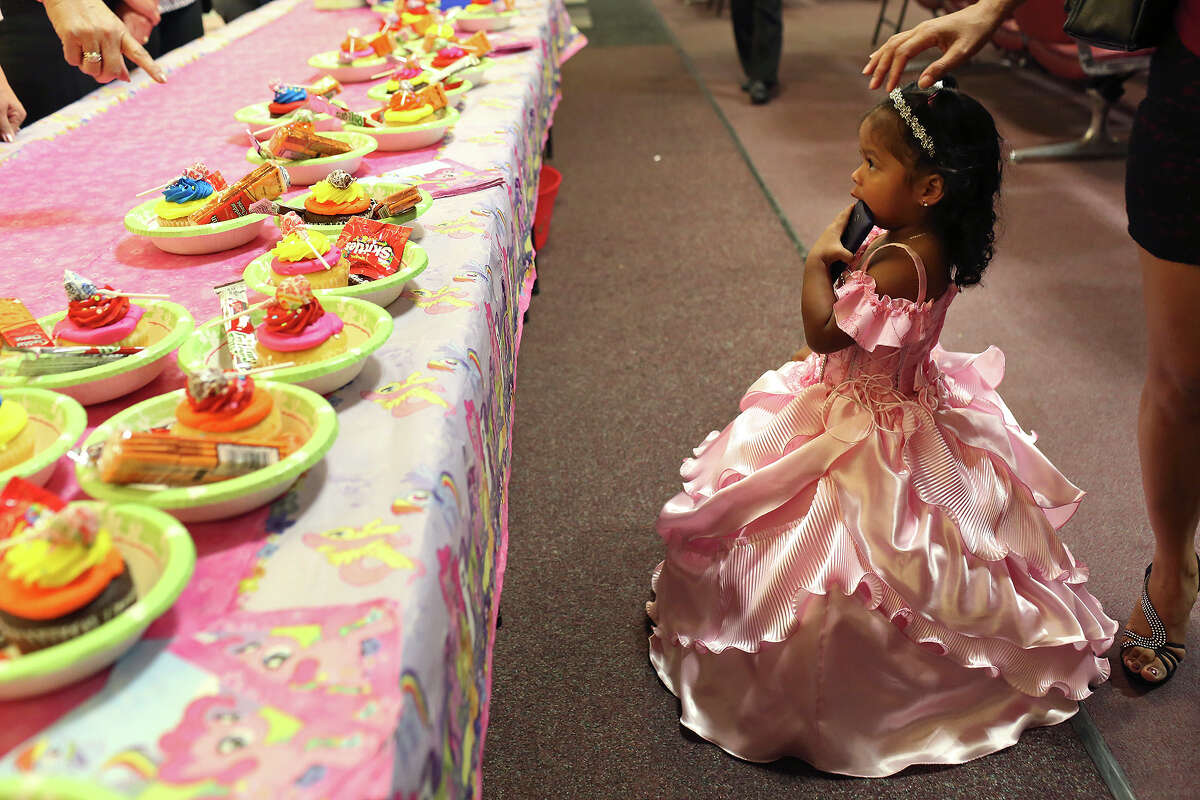 Chasity Martinez, 2, eyes the cupcakes for adoptive children and their families after she was official adopted during the monthly adoption ceremony in the Central Jury Room at the Bexar County Justice Center in San Antonio on Friday, March 7, 2014.