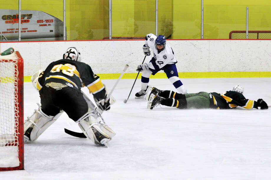 Darien's Jack Pardue skates around Trinity Catholic's Colin Bernard to get a shot on goalie Kyle Odierno during their FCIAC semifinal hockey game at Terry Conners Rink in Stamford, Conn., on Wednesday, March 5, 2014. Photo: Jason Rearick / Stamford Advocate