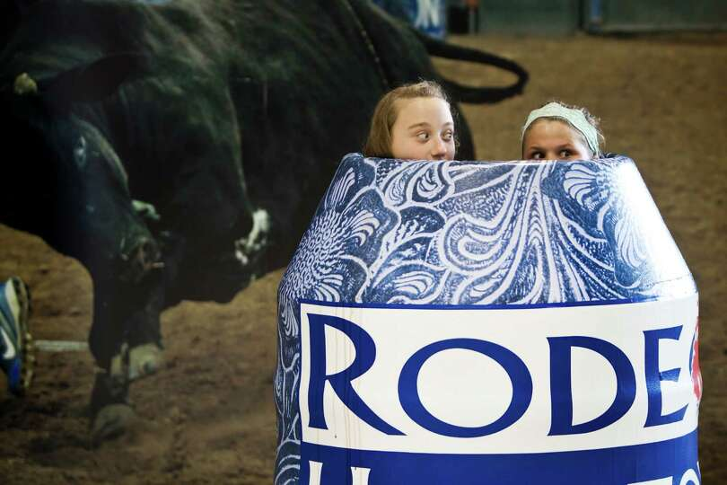 Zoe Rogers, left, 11, and Ashley Kennedy, 12, goof around inside a rodeo barrel for a family photogr