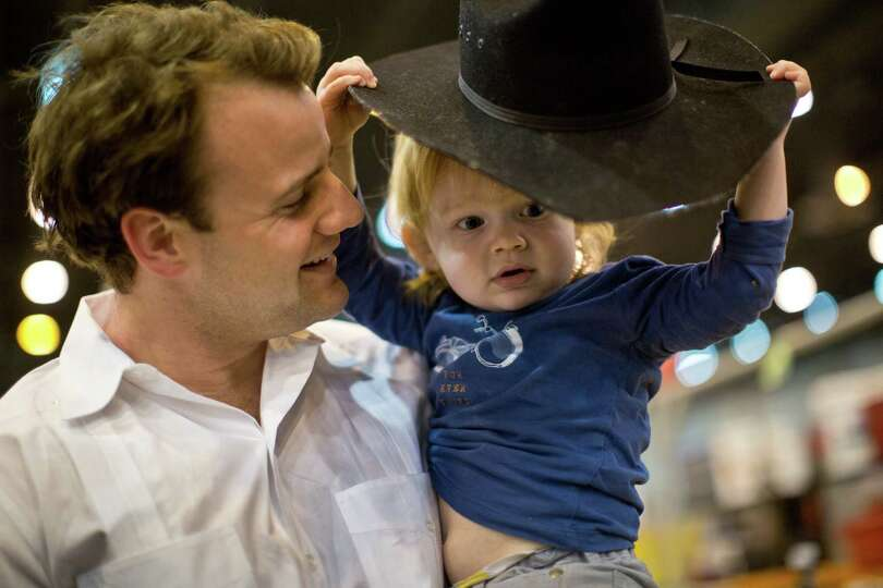 Arthur Caldwell, 2, is about done with his cowboy on the arms of his father Kent Caldwell of Houston