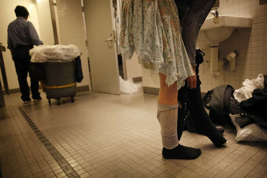 Top: Molly, who is homeless, changes clothes in the Main Library's restroom. Photo: Lea Suzuki, The Chronicle