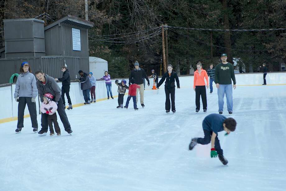 A youngster takes a tumble, first-time skaters stumble, and parents and children work their way around the Curry Ice Rink in Yosemite Valley. The rink will be moved but kept open. Photo: Tom Stienstra