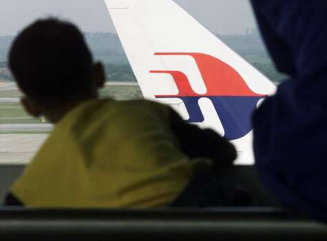 A boy looks at a Malaysian Airlines plane from the viewing gallery of the Kuala Lumpur International Airport in Sepang, in this January 8, 2002 file picture. A Malaysia Airlines flight carrying 227 passengers and 12 crew lost contact with air traffic controllers early on March 8, 2014 en route from Kuala Lumpur to Beijing, the airline said in a statement. Flight MH 370, operating a Boeing B777-200 aircraft departed Kuala Lumpur at 12.21 a.m. (1621 GMT Friday) and had been expected to land in the Chinese capital at 6.30 a.m. (2230 GMT) the same day. Photo: Bazuki Muhammad, Reuters
