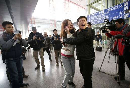 A woman (C), believed to be the relative of a passenger onboard Malaysia Airlines flight MH370, cries as she talks on her mobile phone at the Beijing Capital International Airport in Beijing, March 8, 2014. The Malaysia Airlines Boeing B777-200 aircraft carrying 227 passengers and 12 crew lost contact with air traffic controllers early on Saturday en route from Kuala Lumpur to Beijing, the airline said in a statement.  Photo: Kim Kyung-hoon, Reuters