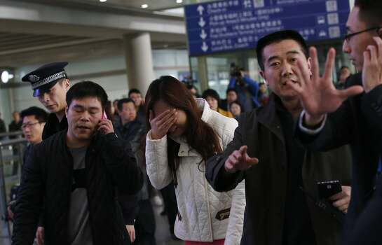 A woman (C), believed to be the relative of a passenger onboard Malaysia Airlines flight MH370, covers her face as she cries at the Beijing Capital International Airport in Beijing March 8, 2014. The Malaysia Airlines flight carrying 227 passengers and 12 crew lost contact with air traffic controllers early on Saturday en route from Kuala Lumpur to Beijing, the airline said in a statement. REUTERS/Kim Kyung-Hoon  Photo: Kim Kyung-hoon, Reuters