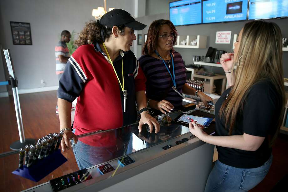 Brenda Calana (left) and Teresa Hernandez speak with sales associate Maylynn Moreno as they shop for electronic cigarettes in Miami. Photo: Joe Raedle, Getty Images