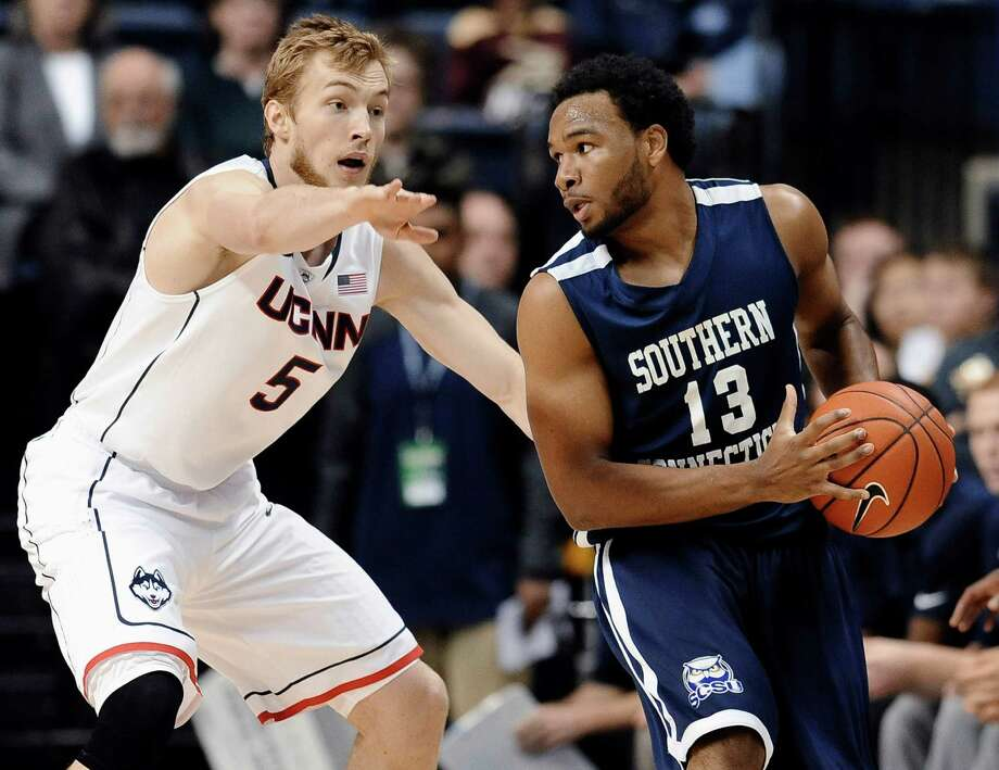 Southern Connecticut's Greg Langston, right, looks to pass as Connecticut's Niels Giffey defends during the first half of an NCAA college exhibition basketball game, Wednesday, Oct. 30, 2013, in Storrs, Conn. Langston was top scorer for Southern Connecticut with 18 points. Connecticut won 93-65. (AP Photo/Jessica Hill) Photo: Jessica Hill, Associated Press / Associated Press