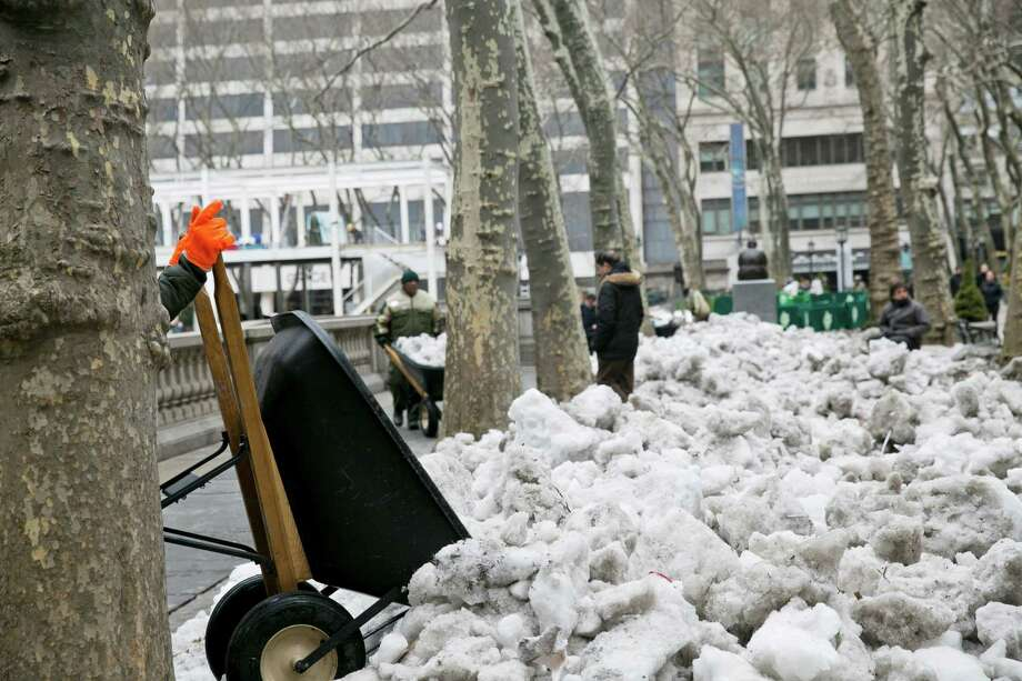 Workers clear chunks of ice and snow in Bryant Park in New York, March 7, 2014. The copious snow and ice that befell much of New York City and the region this winter exacted a financial price that is just now becoming clear. (Todd Heisler/The New York Times) ORG XMIT: XNYT84 Photo: TODD HEISLER / NYTNS