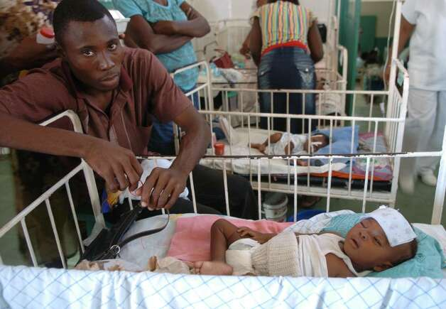 A father sits with his sick child at the Justinien Hospital pediatric ward in Cap-Haitien. Photo: Christian Abraham / Connecticut Post