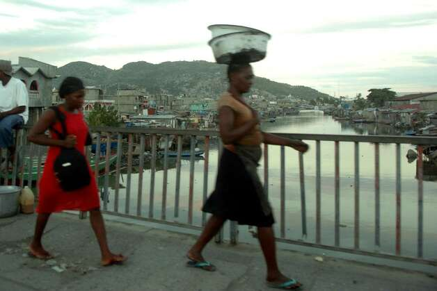 A woman carries a bundle on her head as shet crosses the Mapou River bridge. The slums can be seen along the river banks. Photo: Christian Abraham / Connecticut Post