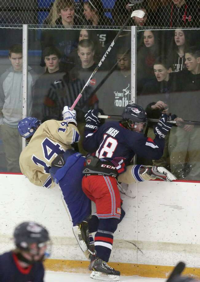 New Fairfield / Immaculate's #18 Peter Masi checks Newtown High School's #14 Jonathan Lovom into the boards during Friday evening's SWC/ SCC Division 1 hockey championship.  New Fairfield / Immaculate would win 2-1. Photo: Mike Ross / Mike Ross Connecticut Post freelance -www.mikerossphoto.com