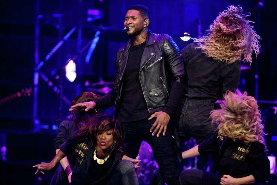 Surrounded by dancers, Usher breaks out in sweat during his Friday night performance at RodeoHouston. Photo: Marie D. De Jesus, Staff / © 2014 Houston Chronicle