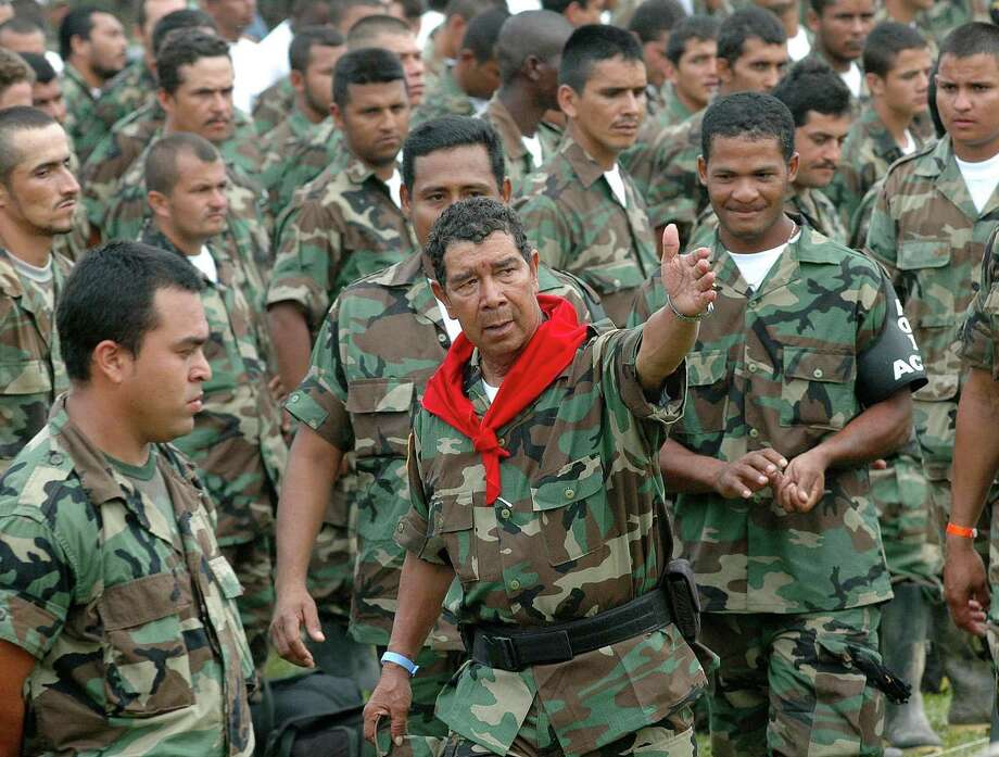 In 2007, militia commander Ramon Isaza (center) rallies his men before turning in their guns during a disarmament ceremony in Colombia. Hundreds of right-wing paramilitaries are expected to walk free from prison starting this month after serving eight-year sentences for crimes that normally carry more than triple the time. Isaza is due to be released in October. Photo: Luis Benavides / Associated Press / AP