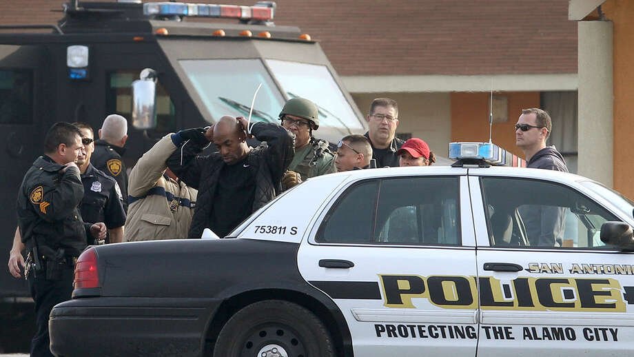 San Antonio police take a man into custody after a standoff with police at the Roosevelt Inn Motel at 2122 Roosevelt. The man was arrested after being suspected of being involved in a robbery of a man who was in a motel room with a prostitute, police say. Photo: John Davenport / San Antonio Express-News / ©San Antonio Express-News/Photo may be sold to the public