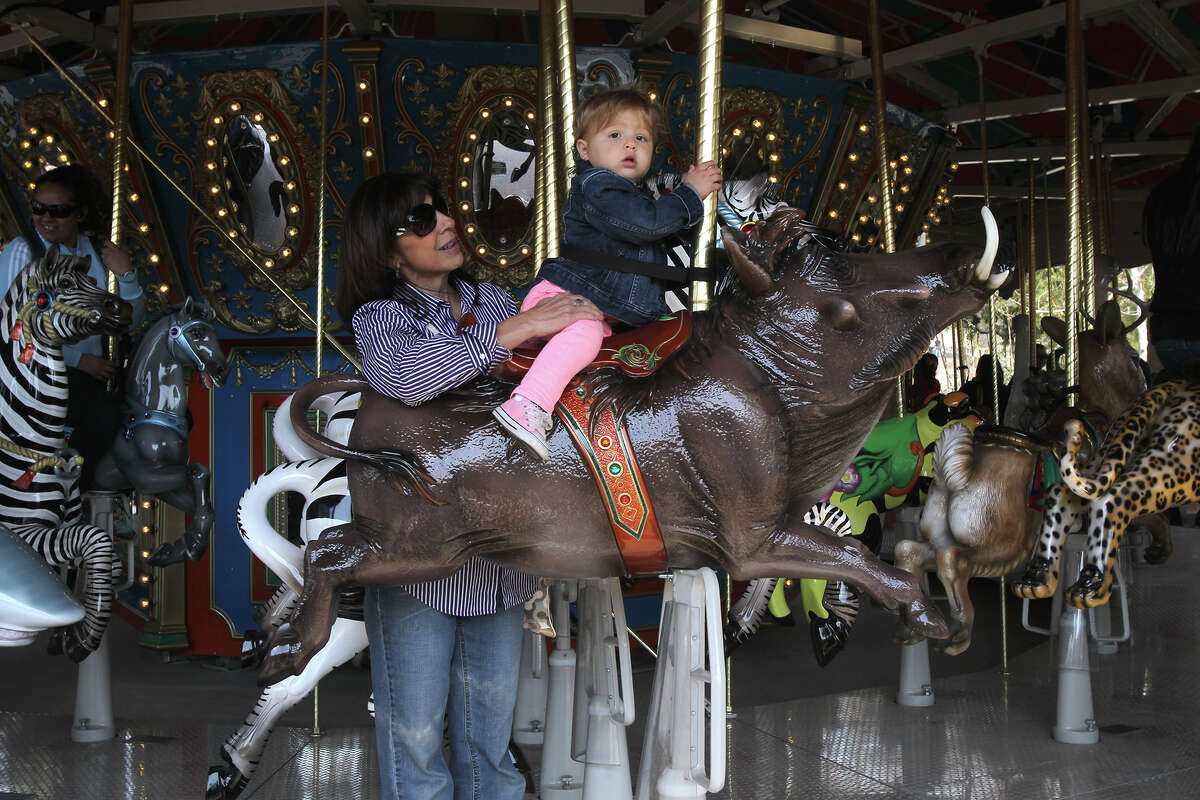 Blake Barnes,15 months, prepares to ride the new carousel Friday March 7, 2014 at the new Zootennial Plaza at the San Antonio Zoo with her grandmother Cindy Horgan (left). The Zootennial plaza opened to mark the zoo's 100th anniversary.