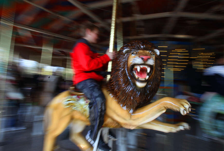 A smiling boy on a lion figure whirls by on the new carousel introduced at the opening of Zootennial Plaza at the San Antonio Zoo. The new $8 million project, which marks the zoo's 100th anniversary, also features a restaurant and gathering area. Photo: JOHN DAVENPORT, SAN ANTONIO EXPRESS-NEWS / ©San Antonio Express-News/Photo may be sold to the public